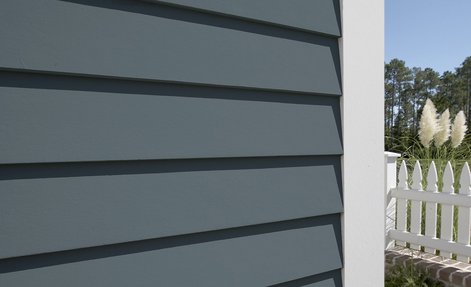 closeup image of gray siding with white trim and white picket fence