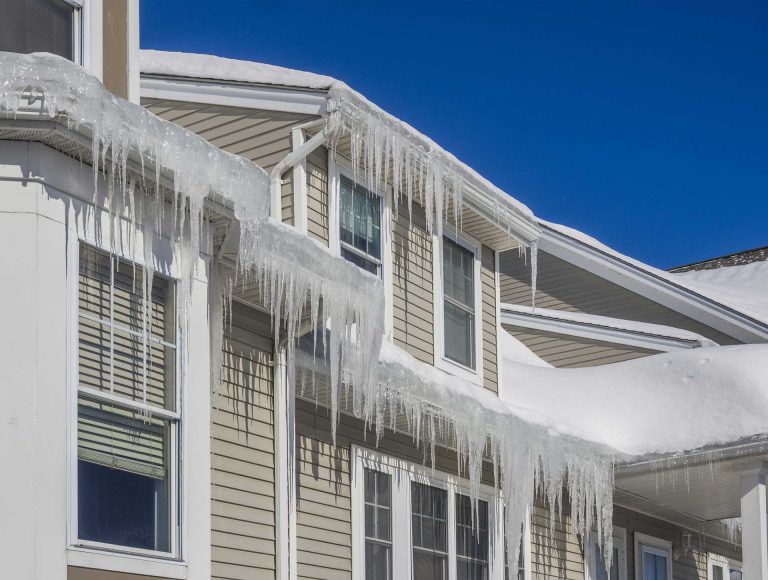 Long icicles on home with beige siding